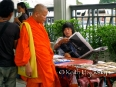 A monk shops at the Buddha amulet market - several blocks full of vendor stalls selling every sort of Buddha stone and amulet possible. copy